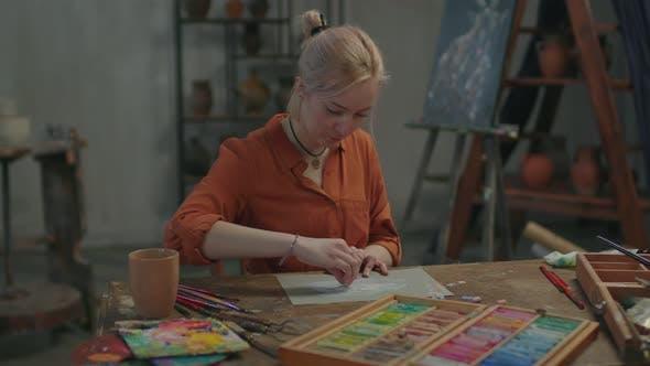 Begabte Malerin mit Streben nach Kreativität, die in der Werkstatt arbeitet