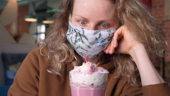 Thumbnail for Woman Wearing Protective Face Mask In Cafe Looking At Pink Coffee Latte With Whipped Cream