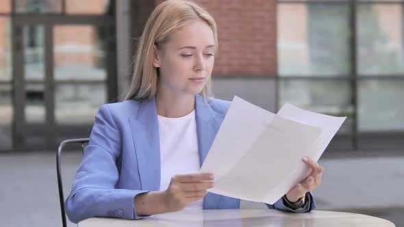 Thumbnail for Young Businesswoman Reading Documents while Sitting Outdoor