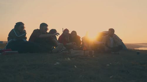 Joyful Hikers Spend Time at Camping with Burning Bonfire