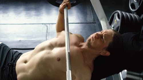Shirtless Muscular Man Doing Barbell Bench Press Exercise at the Gym