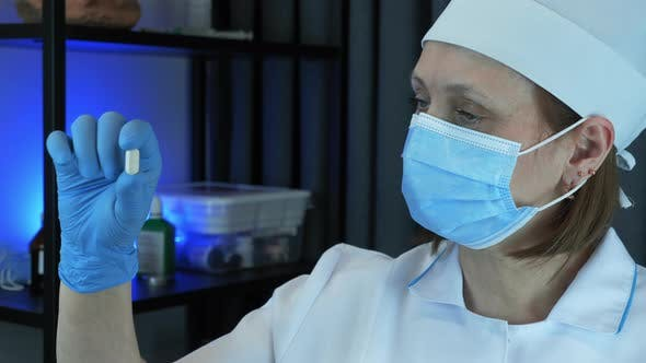 Thumbnail for Female doctor in protective medical face mask, clothes and cap is holding pill in hand