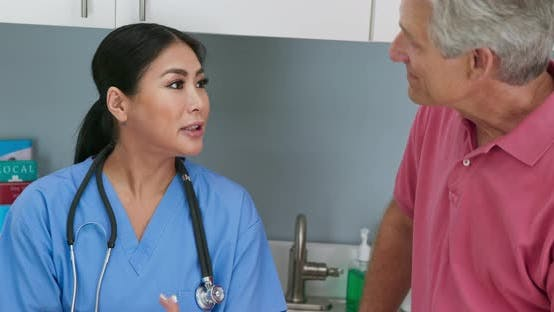 Thumbnail for Surgeon talking to senior patient about surgery and recovery plan in exam room