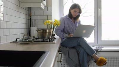 Businesswoman preparing breakfast in a minimalist white kitchen.