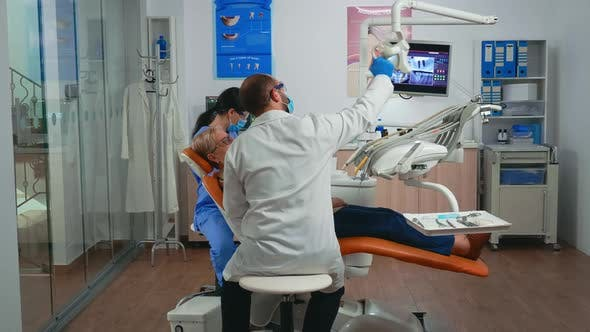 Oral Surgeon Performing Surgery Installing Implant