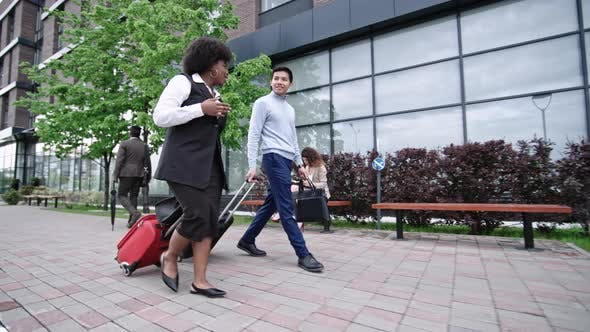 Thumbnail for Business Partners Walking with Suitcases along Glass Building