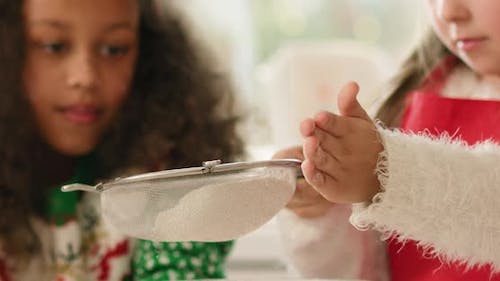 Close up of little girl sifting flour