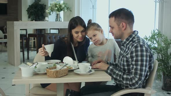 Thumbnail for Young Family Using Laptop, Chatting and Smiling in Cafe or Restaurant