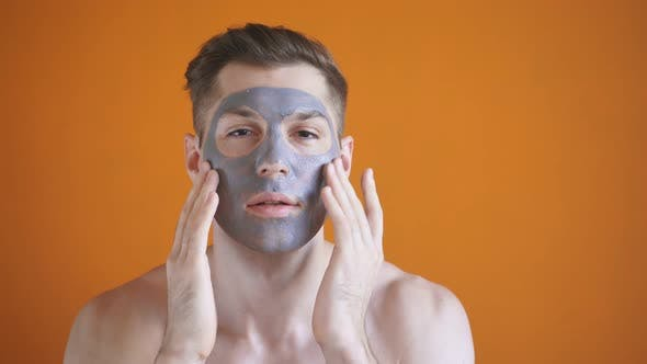 Handsome Man with a Gray Clay Mask on His Face Poses for the Camera on an Isolated Yellow Background