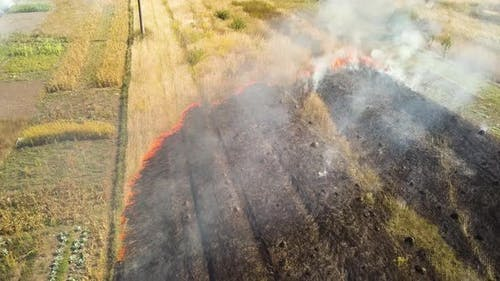 Aerial view of burning grass in field.