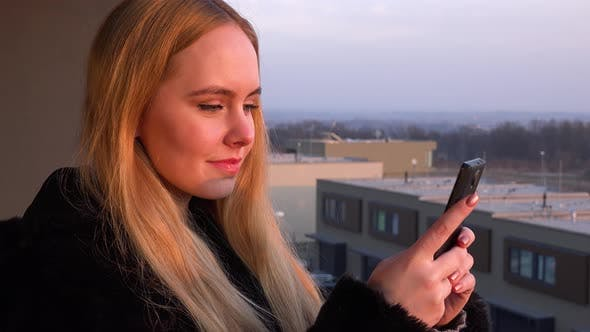 Thumbnail for A Young Beautiful Woman Stands on a Balcony and Works on a Smartphone - Closeup
