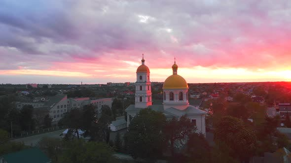 Thumbnail for Small Church at the Bright Cloudy Sunset Filmed By Drone in Small European City. Kyiv Region