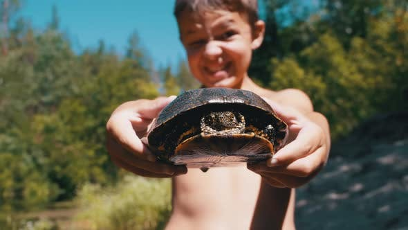 Thumbnail for Boy Holds Turtle in Arms and Smiles Viciously on River with Green Vegetation