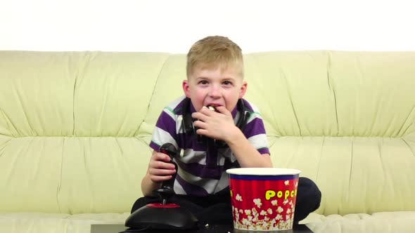 Boy Plays Joystick Online Game and Eats Popcorn, Slow Motion