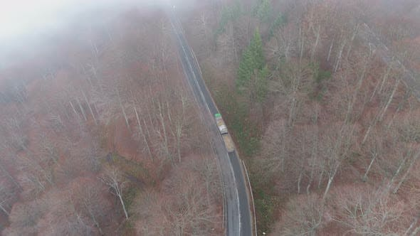 Thumbnail for Heavy Loaded Truck Driving Uphill in Mountain Forest in Misty Autumn Day, Drone View