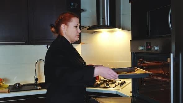 Bäckereiarbeiter Putting Ofen-Tablett mit Keksen in den Ofen