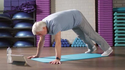 Senior Exercising According to Video Lesson