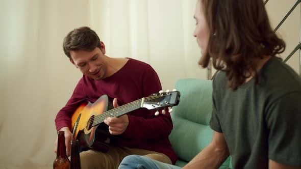 Two Friends are Playing Guitar and Singing Songs