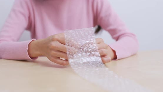 Thumbnail for Woman play with bubble wrap to relief stress