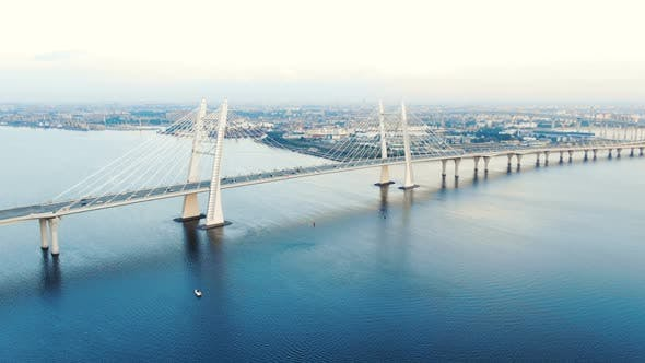 Cable-stayed Bridge and Cars Speeding Against Cityscape
