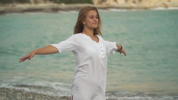 Cover Image for Young Pretty Girl Stands on the Seashore, Spreading Arms, Smiling and Enjoing the Sea Breeze