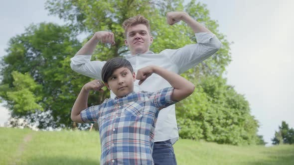 Thumbnail for Portrait Cute Young Father and Adorable Boy Showing Muscles Looking Into the Camera Outdoors. Father