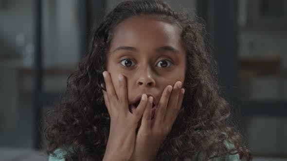 Amazed Little Black Girl Holding Cheeks By Hand