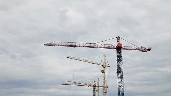 Thumbnail for Cranes Working on Construction Site Under Grey Cloudy Sky on a Rainy Day Timelapse