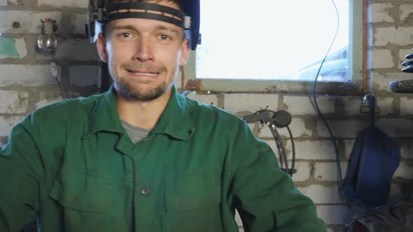 Young Repairman Taking Off Protective Eyewear and Showing Grimaces Into Camera