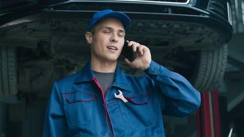 Junge Mechaniker sprechen auf dem Handy beim Wartungsservice, diskutieren Autoschäden mit dem Kunden
