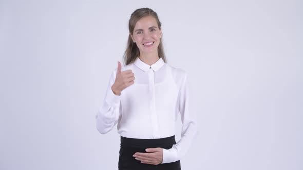 Cover Image for Young Happy Pregnant Businesswoman Giving Thumbs Up