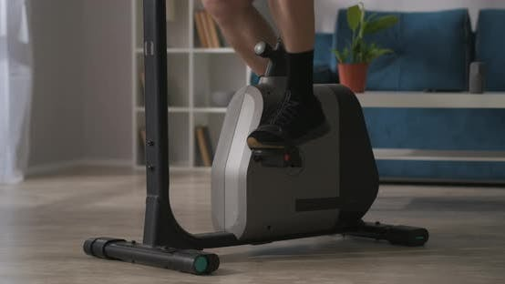 Thumbnail for Person Is Training Alone in Home Using Stationary Bike for Keeping Fit Closeup of Legs on Pedals