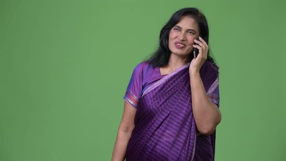 Thumbnail for Mature Happy Beautiful Indian Woman Talking on the Phone While Thinking