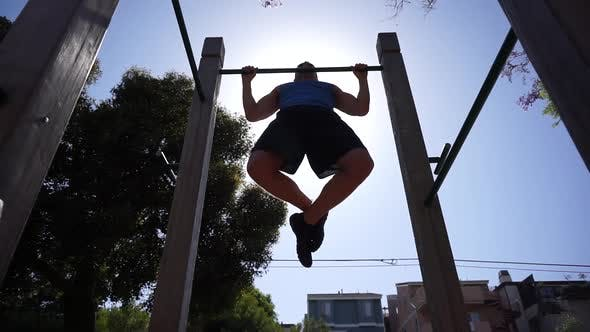 Thumbnail for A man doing pull-ups at a park.