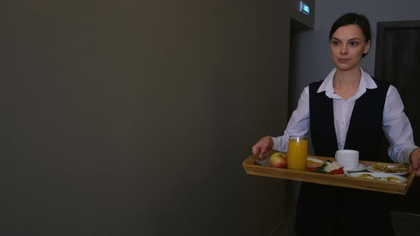 Woman Hotel Worker is Carrying a Breakfast Tray to the Guest's Room
