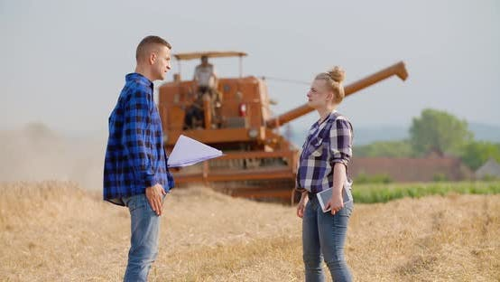 Female Farmer Discussing With Businessman On Farm