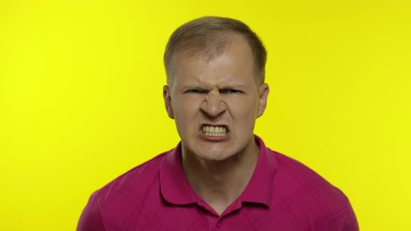 Portrait of Young Caucasian Man Posing in Pink T-shirt. Handsome Guy Screams and Gets Angry