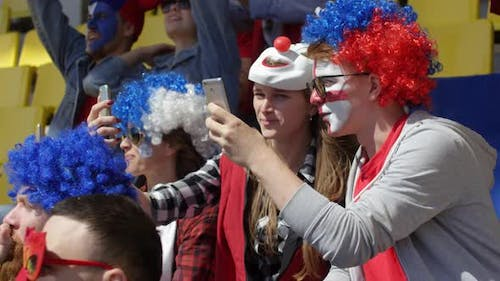 Cheerful Supporters Filming Match on Smartphones