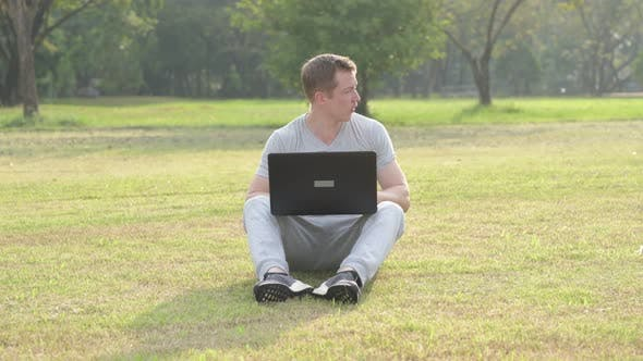 Thumbnail for Young Handsome Man Sitting While Using Laptop at the Park