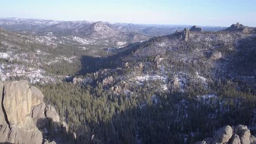 Aerial Drone of Pine Forest in Winter Lake or Pond with Granite Rocks