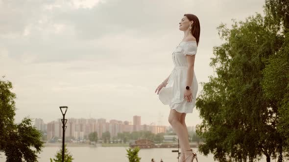 Thumbnail for Cute Woman Walks Along the Embankment Against the Backdrop of the City and the River