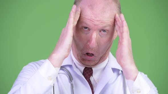Cover Image for Stressed Mature Bald Man Doctor Having Headache
