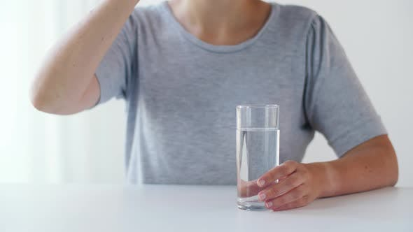 Thumbnail for Woman Taking Medicine and Drinking Water