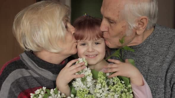 Thumbnail for Grandfather and Grandmother Kissing on Head Their Kid Granddaughter at Home