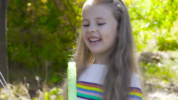 Thumbnail for Little Brunette Girl Staying in Autumn Sun rays and Blowing Soap Bubbles