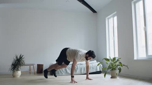 Young Man Practicing Burpee Exercise at Home