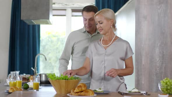 Thumbnail for Middle-Aged Caucasian Woman Making Breakfast and Chatting to Husband