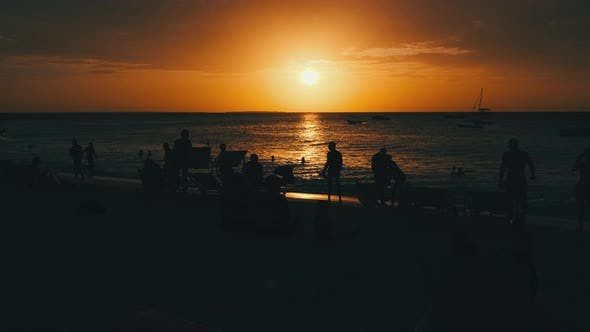 Silhouettes of People at Sunset Having a Rest By Ocean on the Beach Zanzibar