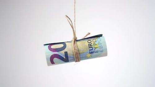 Gerollte Eurorechnungen mit Juteseil gebunden und geschwungen