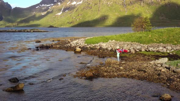 Cover Image for Woman with a Waving Flag of Norway on the Background of Nature